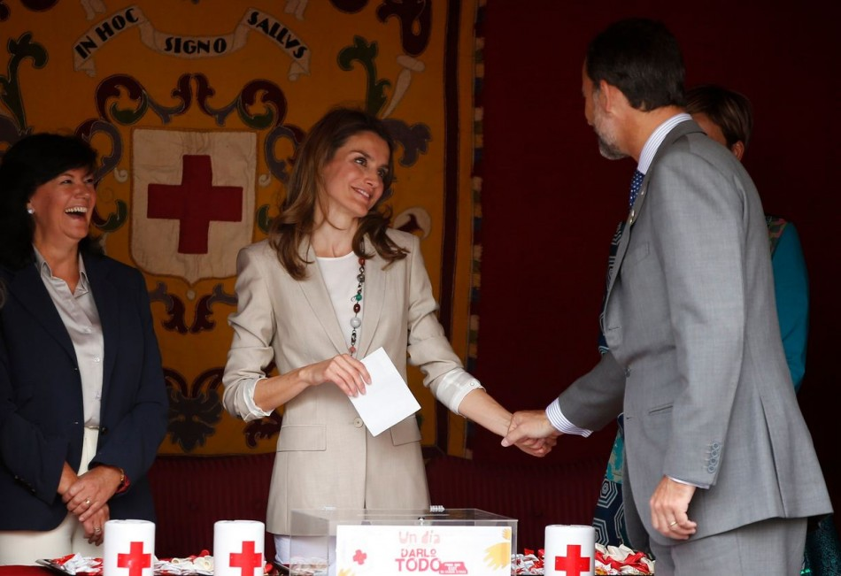 Princess Letizia holds the hand of her husband, Spain's Crown Prince Felipe, as she collects money donations. (Photo: REUTERS/Susana Vera)