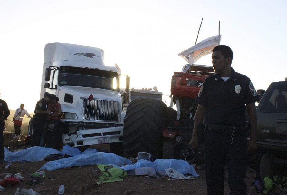 A police officer looks on as bodies lie covered withsheets after a monster truck ploughed into a crowd of spectators in Mexico.