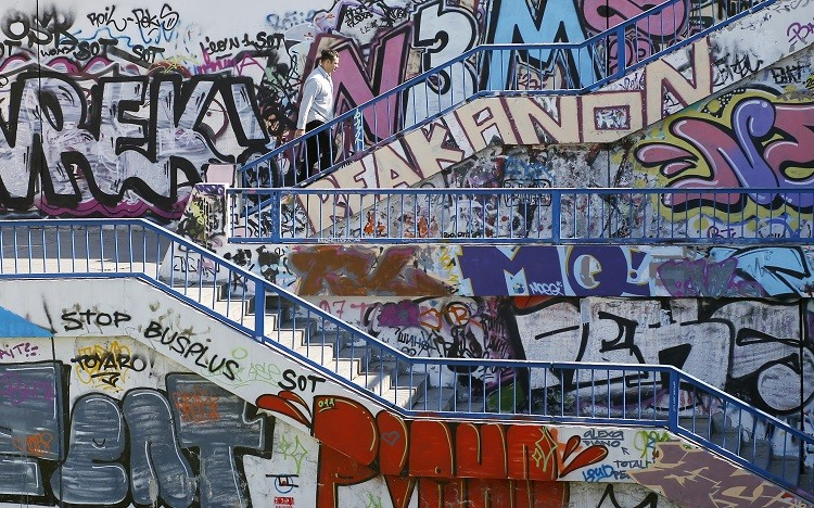 A man walks up a flight of stairs along walls covered in graffiti in Belgrade, Serbia (Photo: Reuters)
