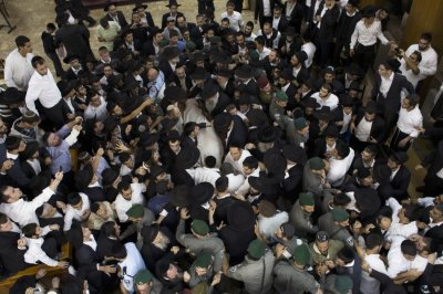Ultra-Orthodox Jewish men gather near the body of Rabbi Ovadia Yosef