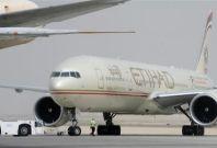 An engineer walks near an Etihad Airways aircraft at Abu Dhabi International Airport, September 19, 2012.