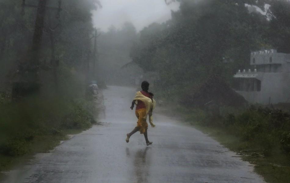 A woman runs for shelter as Cyclone Phailin strikes.