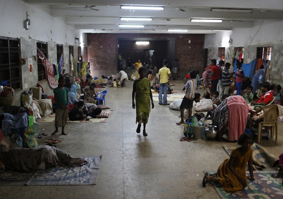 People take shelter at a wedding hall after leaving their houses to take shelter from the impact of the approaching Cyclone Phailin, in the eastern Indian state of Odisha