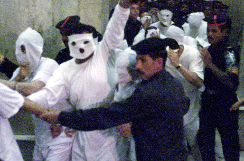 Egyptian security flank 52 suspected homosexual men accused of sexual immorality as they arrive at a Cairo court November 14, 2001