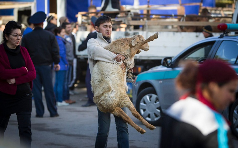 Man carries sheep for slaughtering after a prayer at Kurban-Ait, also known as Eid al-Adha in Arabic, at a mosque in Almaty. (Photo: Reuters)