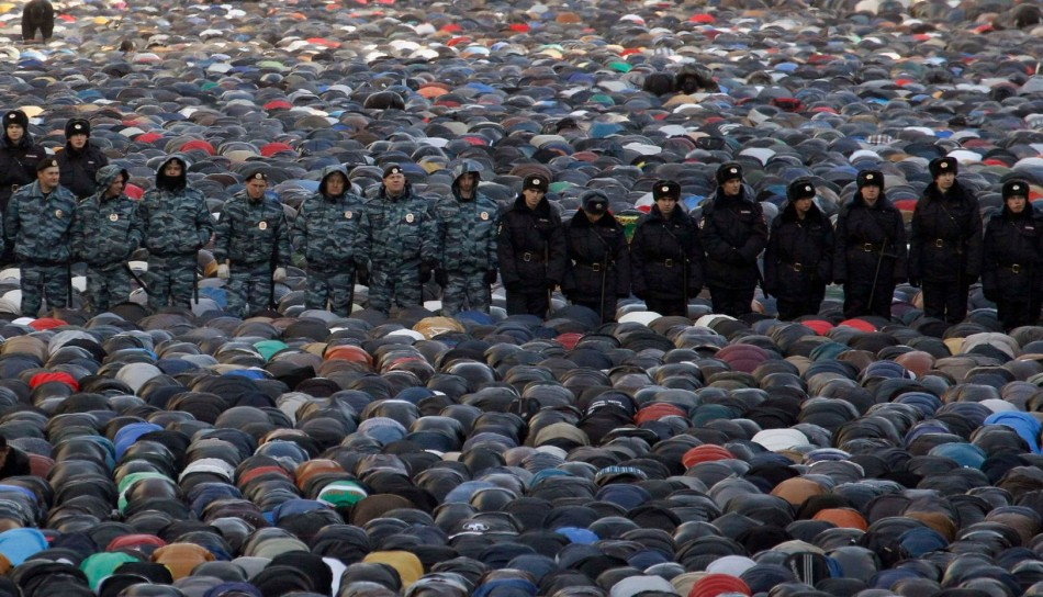 Interior Ministry members stand guard as muslims attend an Eid al-Adha mass prayer in Moscow. (Photo: Reuters)