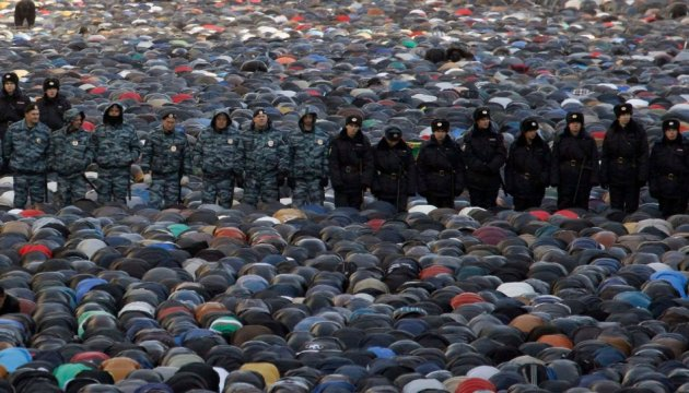 Interior Ministry members stand guard as muslims attend Eid al-Adha prayers in Moscow. (Photo: Reuters)