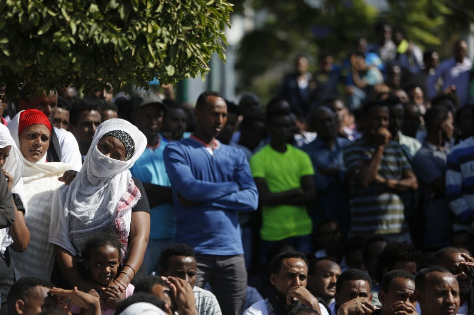 African migrants watch a memorial service for the deaths of hundreds of migrants in last week's Lampedusa boat disaster, in Tel Aviv