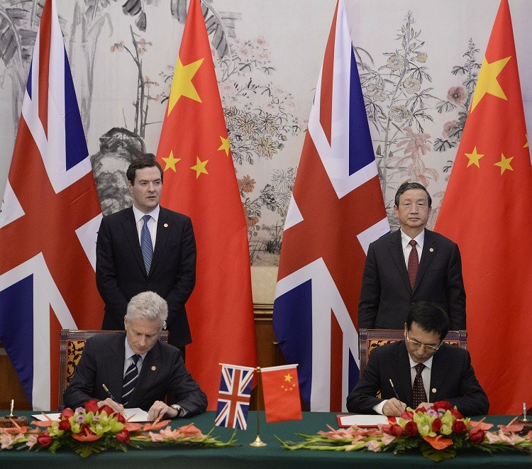 Britain's Chancellor of the Exchequer George Osborne (rear, L) stands next to Chinese Vice premier Ma Kai (rear, R), as Paul Deighton, commercial secretary to the Treasury, participates in a signing ceremony with Xu Yongsheng, deputy director of China's N