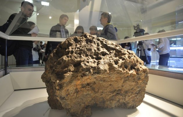 Reporters gather around a piece of a meteorite that crashed in Russia (Reuters)