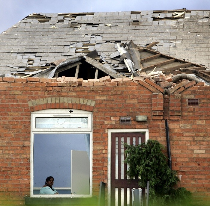 A woman sits in her damaged home after a tornado struck the Moseley area of Birmingham in central England July 28, 2005. (Reuters)