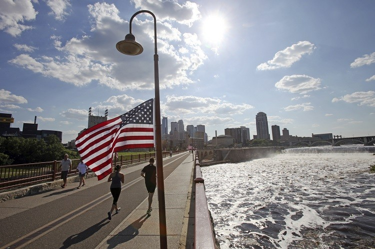 Runners cross the pedestrian-only stone arch bridge that crosses the Mississippi River downstream of the St. Anthony Falls (right) in Minneapolis, Minnesota. (Photo: Reuters)