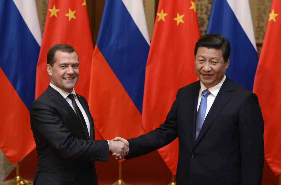Russian Prime Minister Dmitry Medvedev shakes hands with Chinese President Xi Jinping