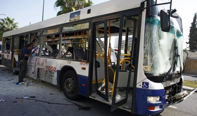 Israeli police officer looks at a damaged bus after an explosion in Tel Aviv (Reuters)