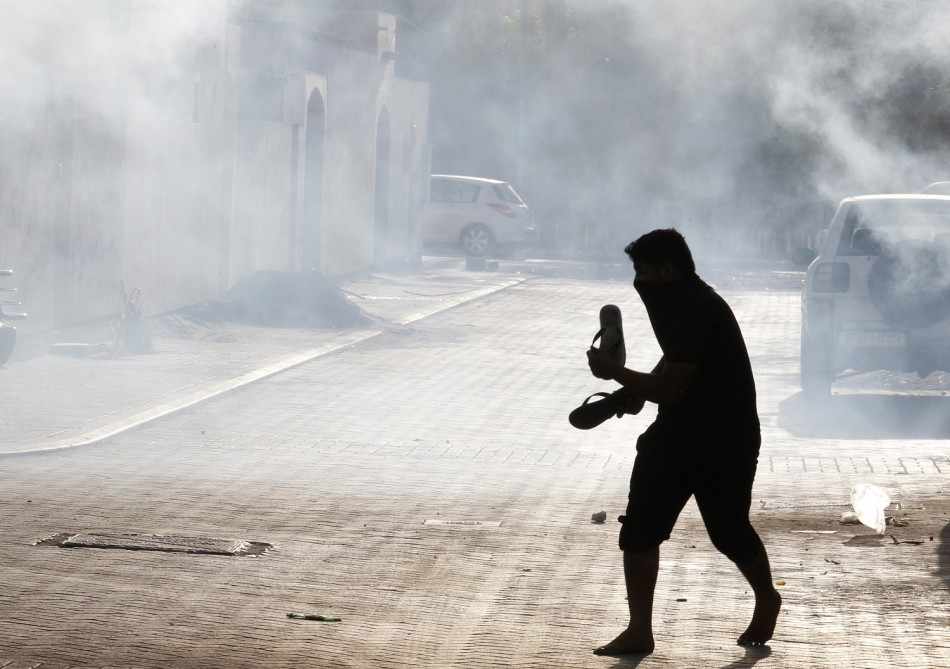 A protester runs to take cover from tear gas fired by riot police during clashes in the village of Maqusha, west of Manama
