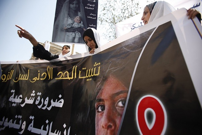 Yemeni women hold up a poster portraying a child bride during a sit-in outside the parliament (Reuters)
