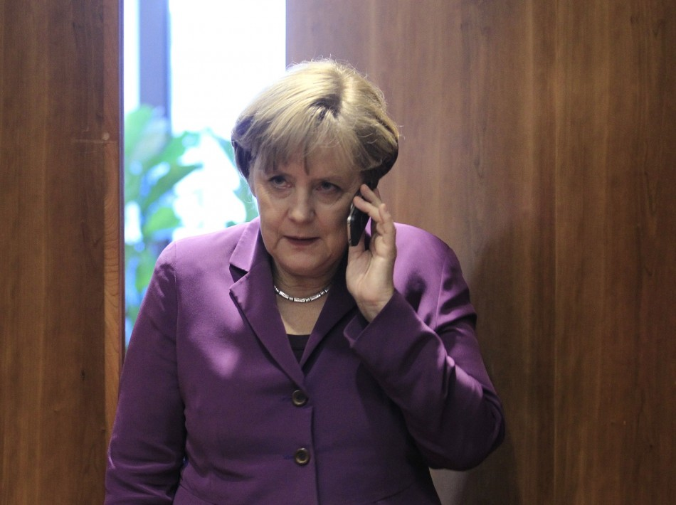 Germany's Chancellor Angela Merkel uses her mobile phone before a meeting at a European Union summit in Brussels