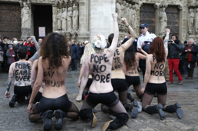 The group protests outside Notre-Dame de Paris Cathedral in Paris to celebrate French parliament's approve a draft law allowing same-sex marriage (Reuters)