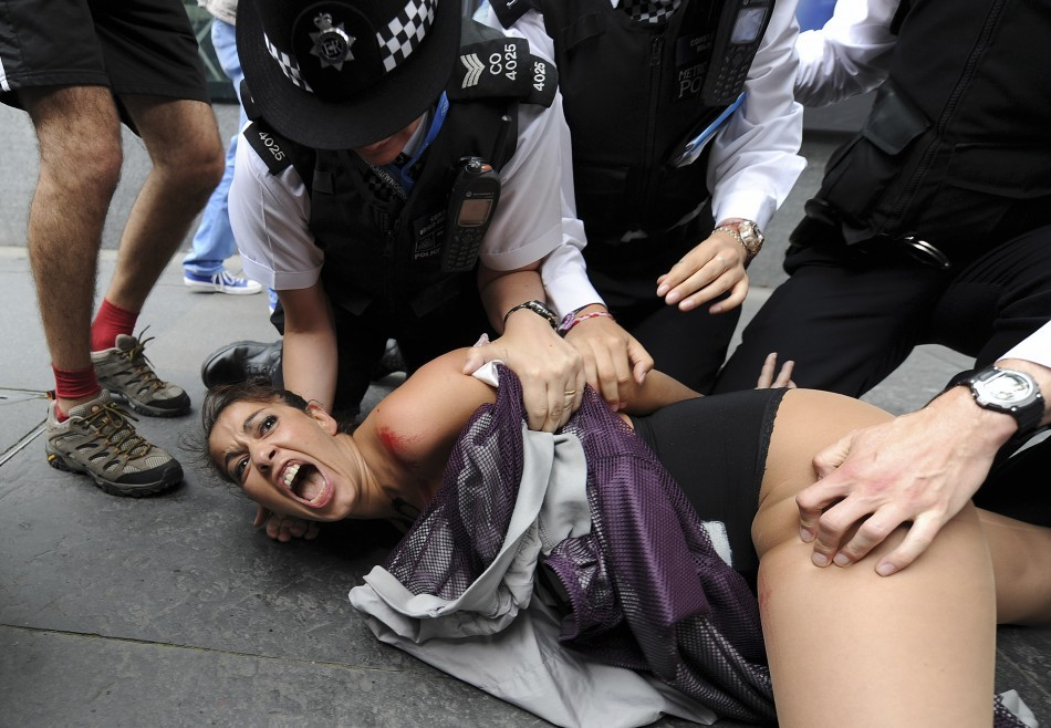 A Femen member is tackled to then group during as protest in London (Reuters)