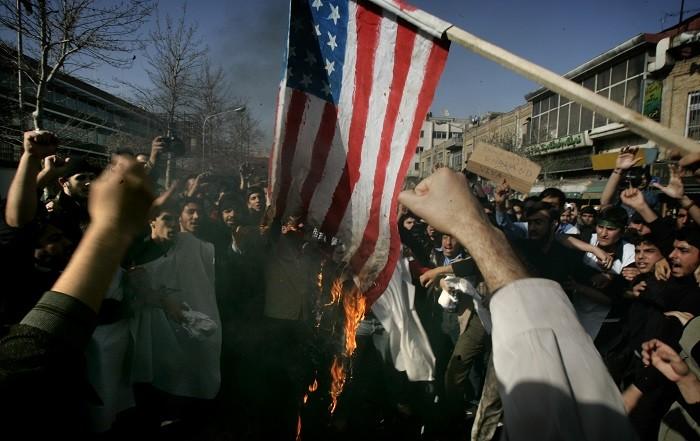 Iranian protestors burn a US flag during a protest in Tehran.