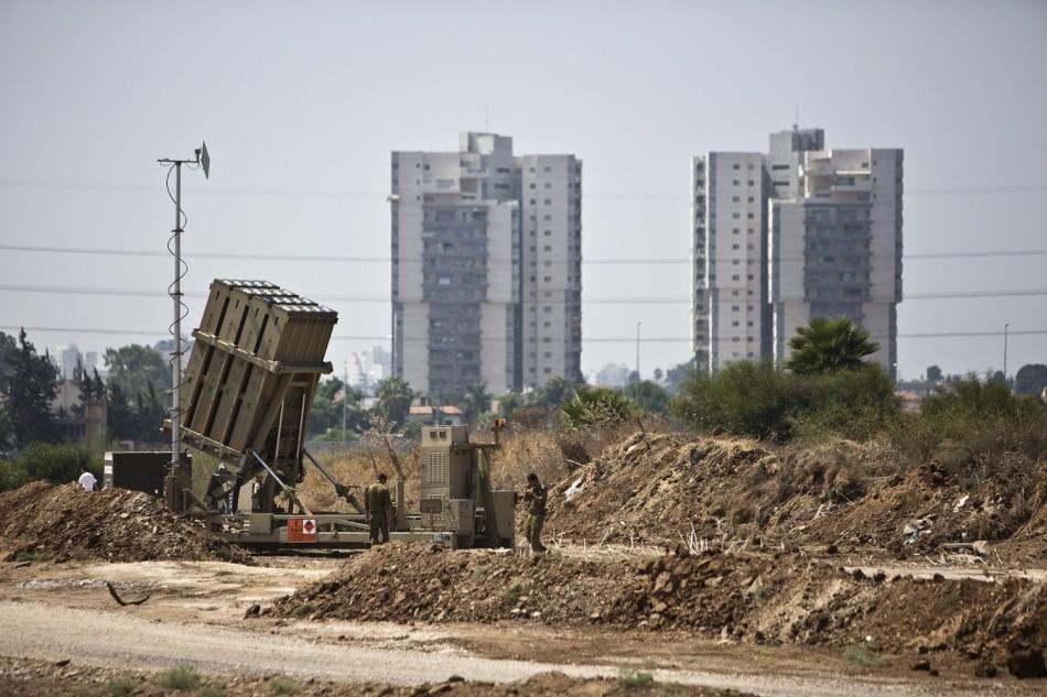 Israeli soldiers walk near an Iron Dome rocket interceptor battery