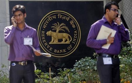 Two men make phone calls while standing near a Reserve Bank of India (RBI) crest at the RBI headquarters in Mumbai January 29, 2013.