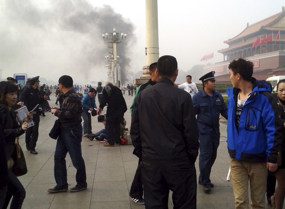 People walk along the sidewalk of Chang'an Avenue as smoke raises in front of the main entrance of the Forbidden City at Tiananmen Square