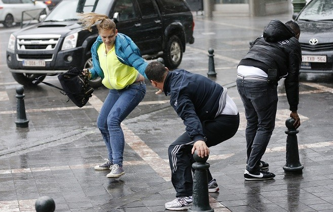 A man helps a woman to cross a square during strong winds in central Brussels (Reuters)