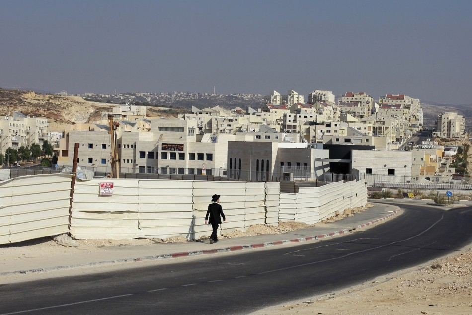 An ultra-Orthodox youth walks past a construction site in the West Bank Jewish settlement of Modiin Illit