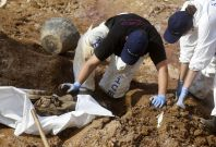 Forensic experts, members of the International Commision of Missing Persons (ICMP) and Bosnian workers search for human remains at a mass grave in the village of Tomasica near Prijedor