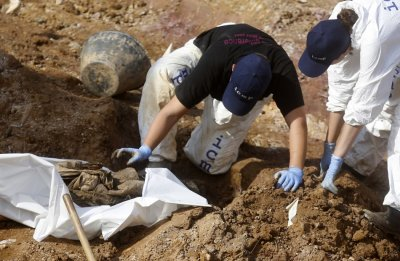 Forensic experts, members of the International Commision of Missing Persons ICMP and Bosnian workers search for human remains at a mass grave in the village of Tomasica near Prijedor