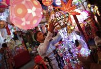 A vendor hangs lanterns for sale at a Diwali market in Mumbai. (Photo: REUTERS)