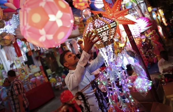 A vendor hangs lanterns for sale at a Diwali market in Mumbai. (Photo: REUTERS)