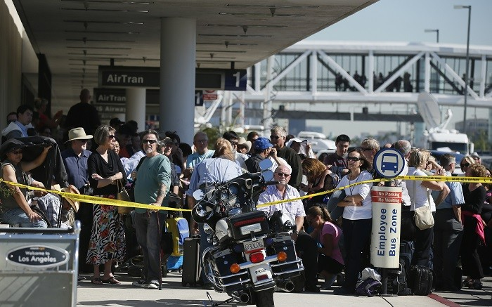 Delayed passengers stand behind a police cordon after a shooting incident at Los Angeles airport. (Picture: Reuters)