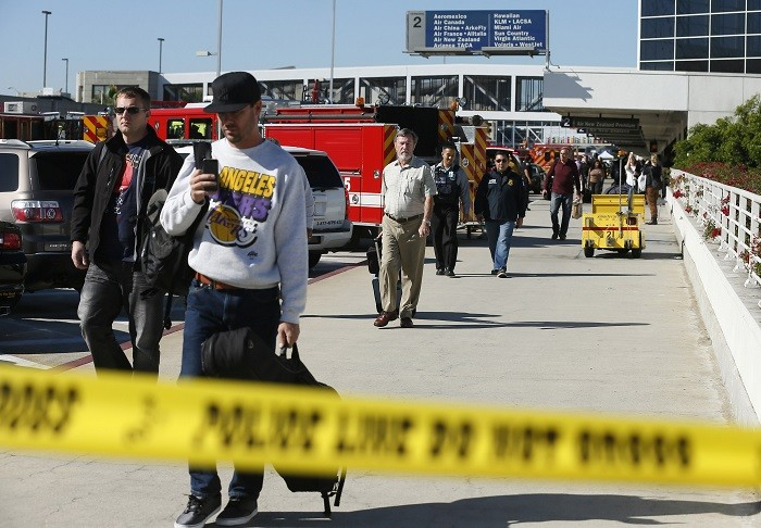 Passengers evacuate after a shooting incident at Los Angeles airport (Picture: Reuters)