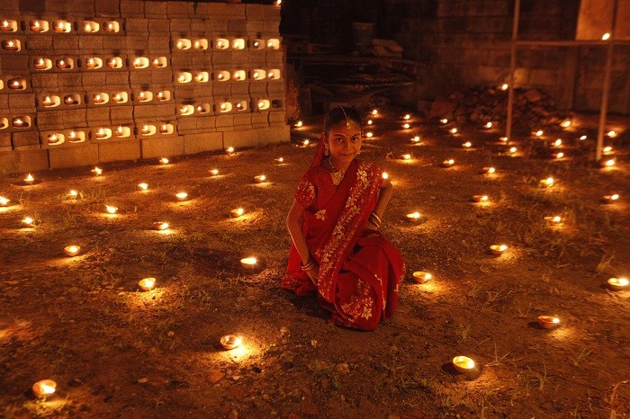 A girl sits among diyas, or oil lamps, in her yard during Diwali celebrations in Felicity, central Trinidad November 13, 2012. (Picture: Reuters)