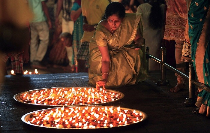 A Tamil devotee lights oil lamps during a religious ceremony to celebrate Diwali at Ponnambalavaneshwaram Hindu temple in Colombo, November 2, 2013. Picture: (Reuters)