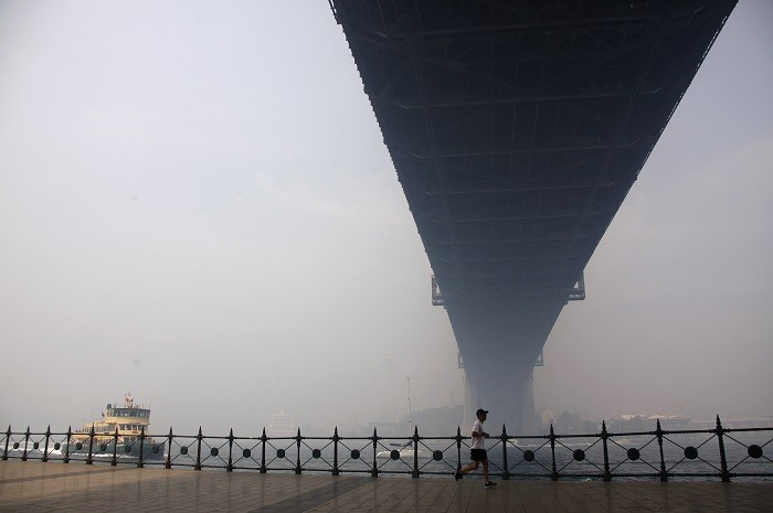 A man jogs beneath a hazy Sydney Harbour Bridge