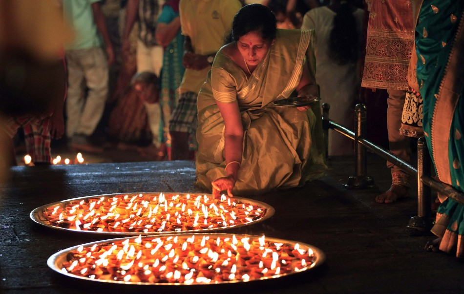 A devotee lights oil lamps during Diwali at a Hindu temple in Colombo. Lighting diyas is the vital tradition of Diwali. (Photo: Reuters)