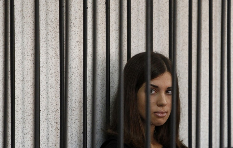 "Member of the female punk band ""Pussy Riot"" Nadezhda Tolokonnikova looks out from a holding cell as she attends a court hearing to appeal for parole at the Supreme Court of Mordovia"