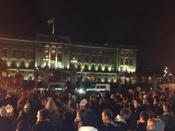 Anonymous protestors congregate in front of Buckingham Palace