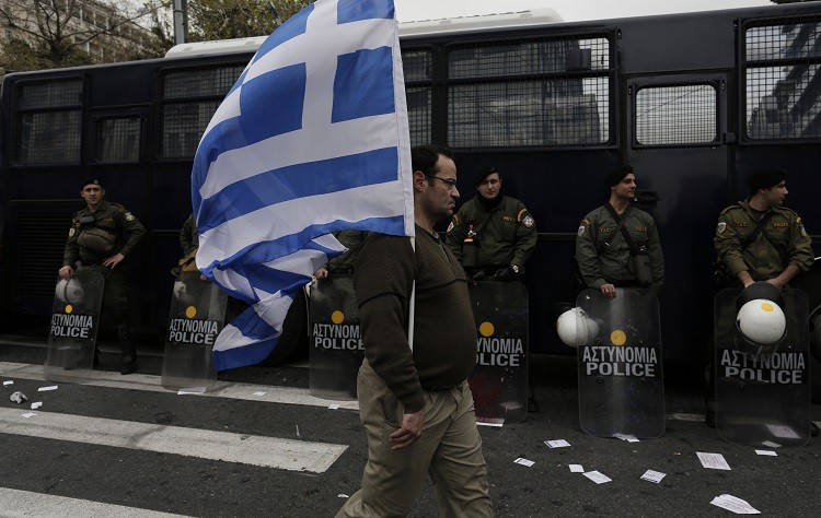 A man holds a Greek flag in front of riot policemen during a military parade to mark Greece's Independence Day in Athens March 25, 2013. (Photo: Reuters)