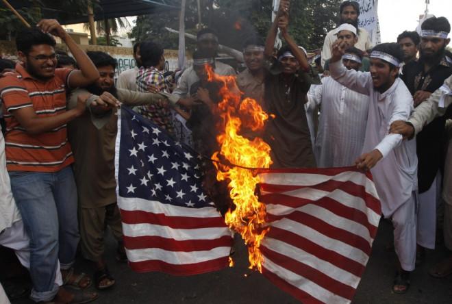 Supporters of the Jamaat-ud-Dawa Islamic organization burn the U.S. flag