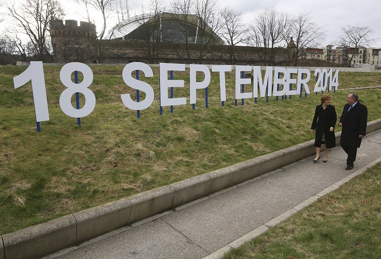 Scotland's First Minister and leader of the Scottish National Party (SNP) Alex Salmond and his deputy leader Nicola Sturgeon walk in front of a sign indicating the date of Scotland's independence referendum outside the Scottish Parliament in Edinburgh, Scotland (Photo: Reuters)