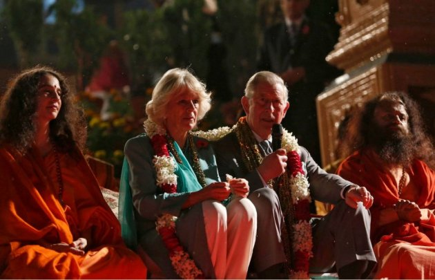 Prince Charles addresses a gathering as Camilla and the sadhus watch after they performed a puja on banks of river Ganges in Rishikesh. (Photo: Reuters)