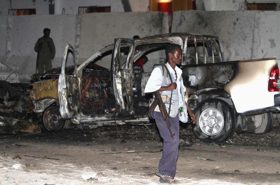 A Somali policeman walks past a burnt car after an explosion outside the Maka Al-Mukarama hotel in Somalia's capital Mogadishu