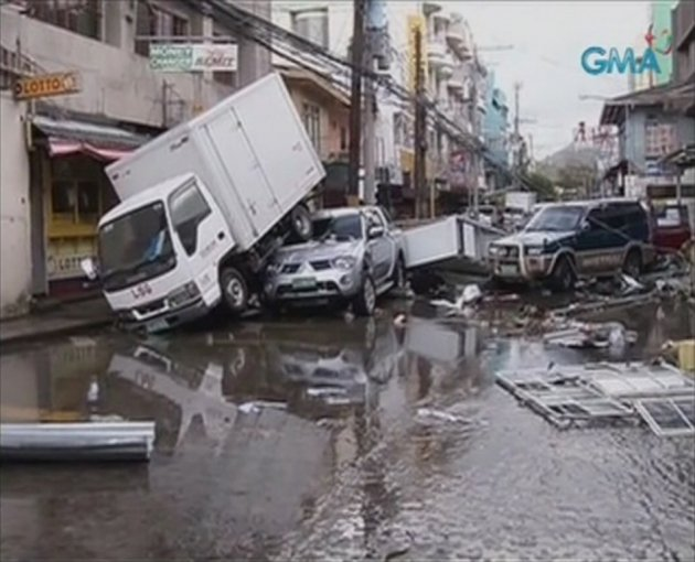 Piled up vehicles are pictured on a flooded street filled with debris after Typhoon Haiyan hit the central Philippine city of Tacloban - (Reuters)