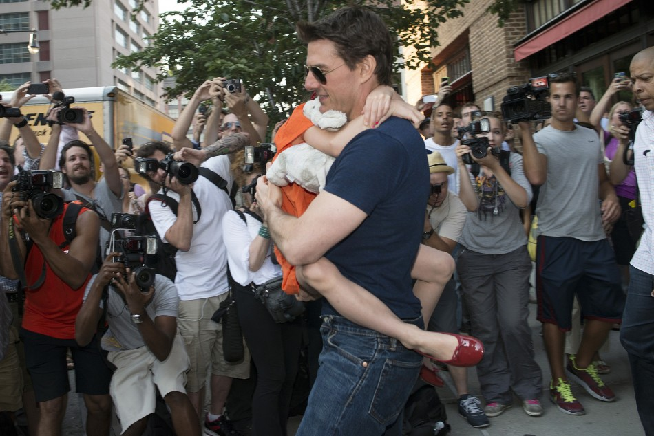 Actor Tom Cruise carries his daughter Suri past a group of photographers.