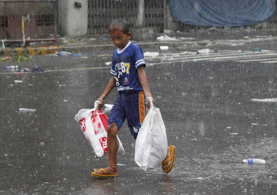 A boy carries relief goods after super Typhoon Haiyan battered Tacloban city