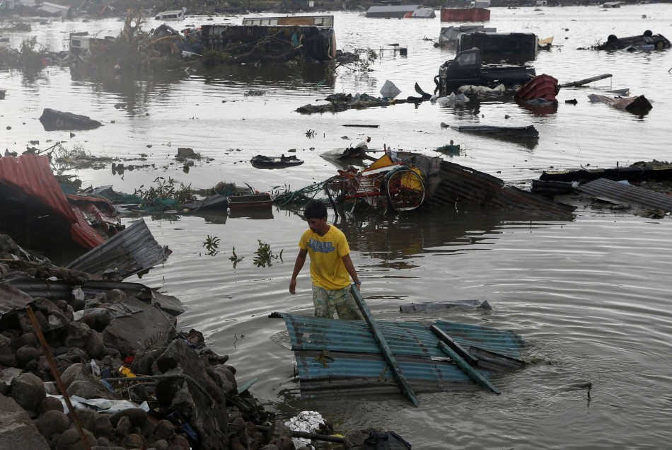 A man retrieves a house roofing from a river after Super Typhoon Haiyan battered Tacloban city in central Philippines